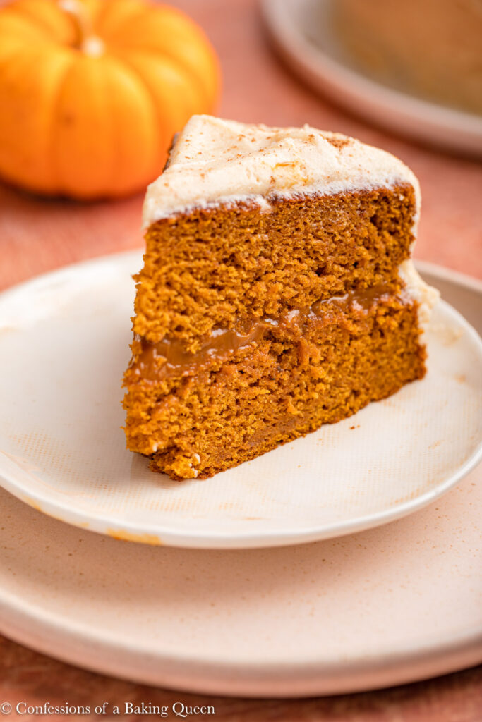 slice of brown butter pumpkin cake on a white plate on a red background with pumpkin in the back