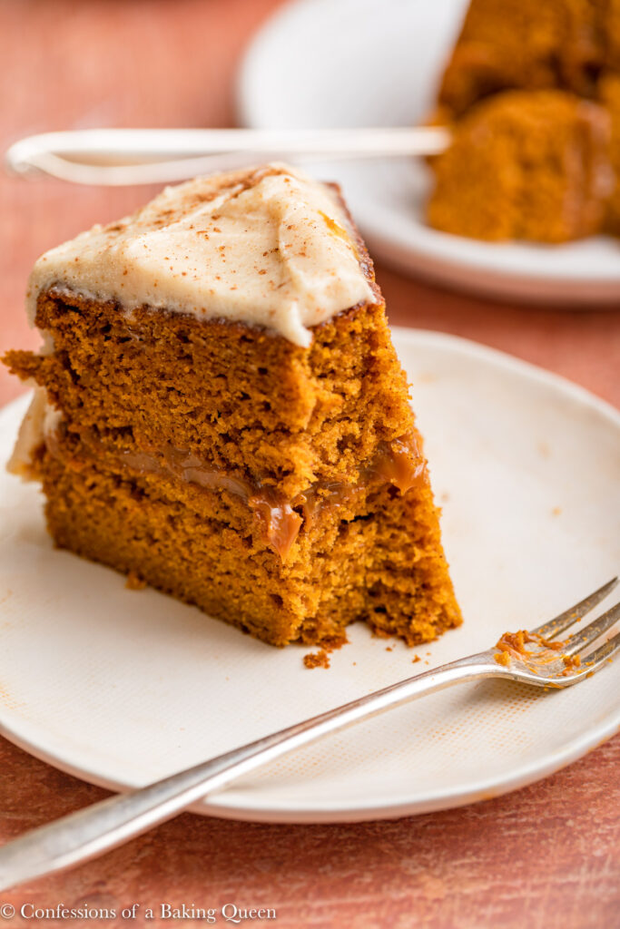 slices of pumpkin dulce de leche cake on white plates with forks on reddish brown surface