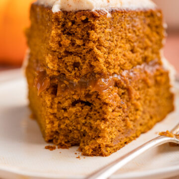 up close of half eaten pumpkin layer cake on a stack of light plates with a fork