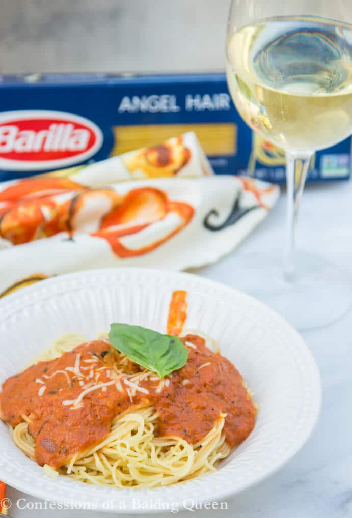 white bowl of Angel Hair Creamy Marinara pasta next to silverware, a glass of white wine, and a box of barilla angel hair pasta on a white and orange linen