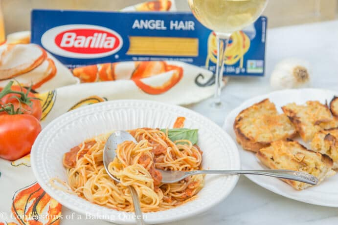 Angel Hair Creamy Marinara pasta in a white bowl with a spoon and fork next to a glass of white wine, plate of garlic bread, tomatoes on a linen and a box of barilla angel hair pasta