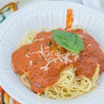 white bowl of Angel Hair Creamy Marinara pasta next to a white and orange linen
