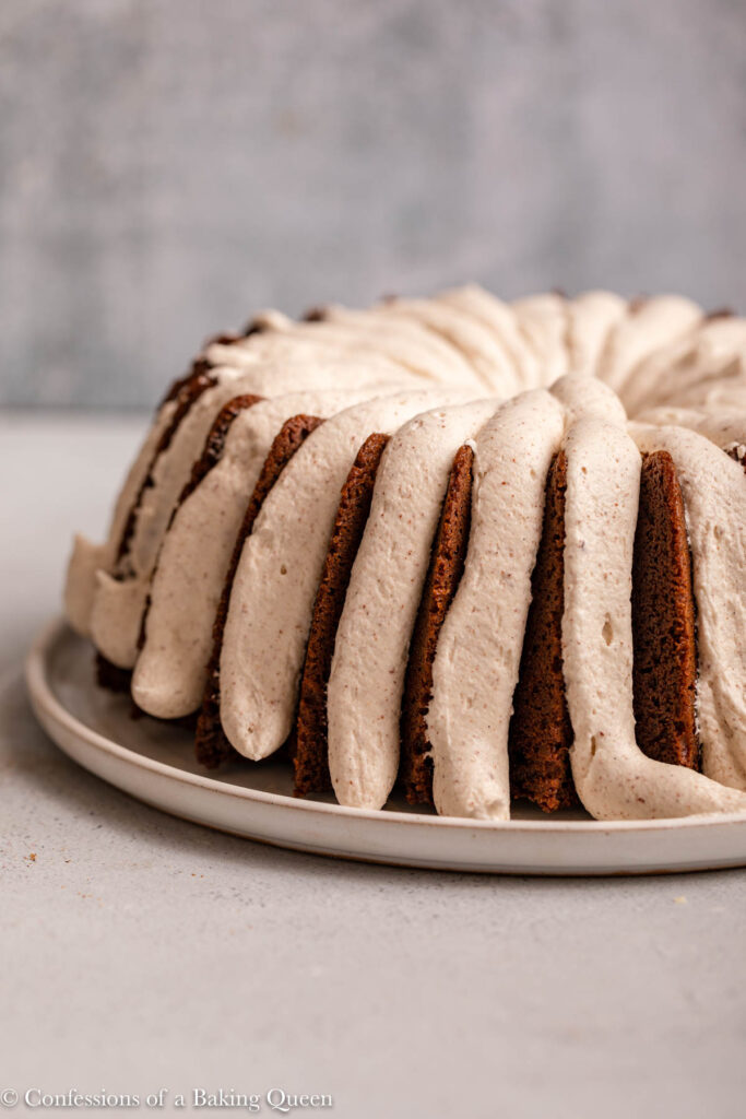 close up of frosted gingerbread bundt cake on a white plate on a light grey surface