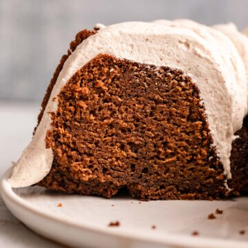 close up of sliced gingerbread bundt cake on a white plate on a light grey background