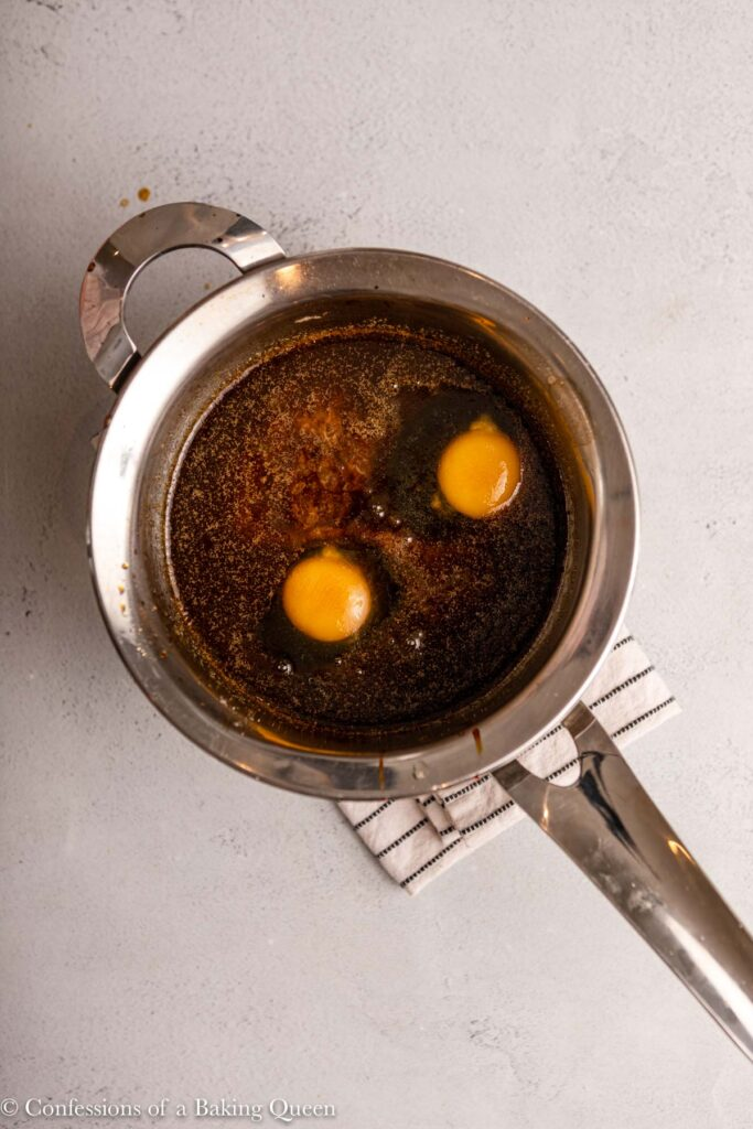 eggs added to wet ingredients in a metal pot on a light grey surface