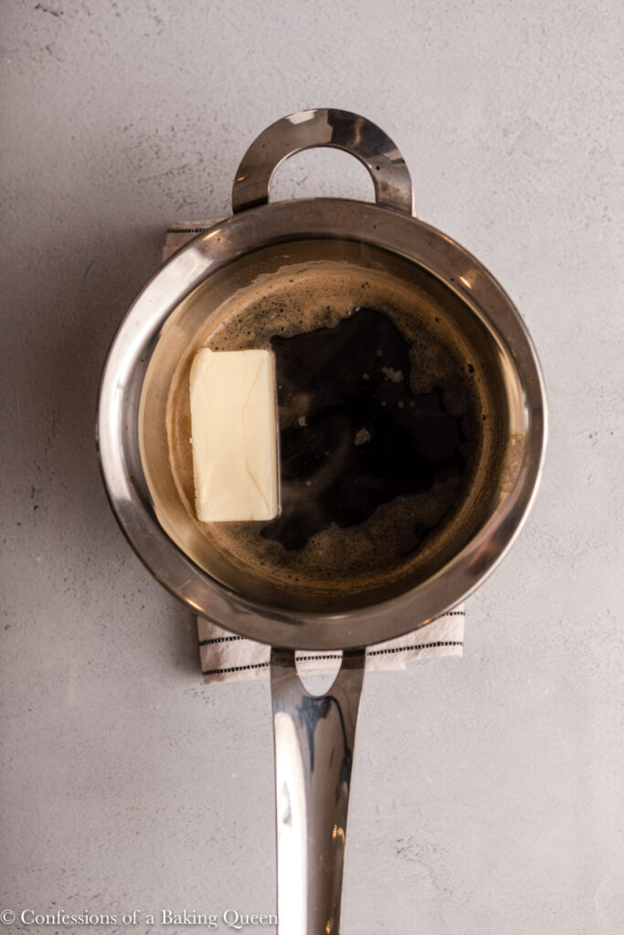 guinness and a stick of butter in a metal pot on a light grey surface