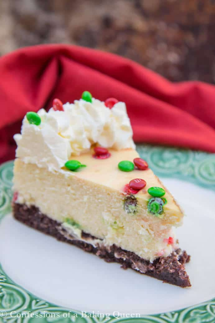 close up of a Brownie Bottom Cheesecake slice on a white plate with a green rim