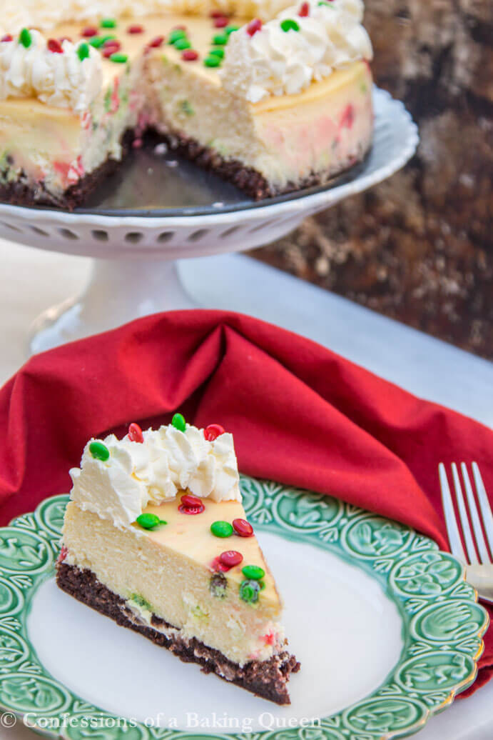 Brownie Bottom Cheesecake on a white and green plate with a red linen and fork next to it on a white surface with the full cheesecake on a white cake plate in the background