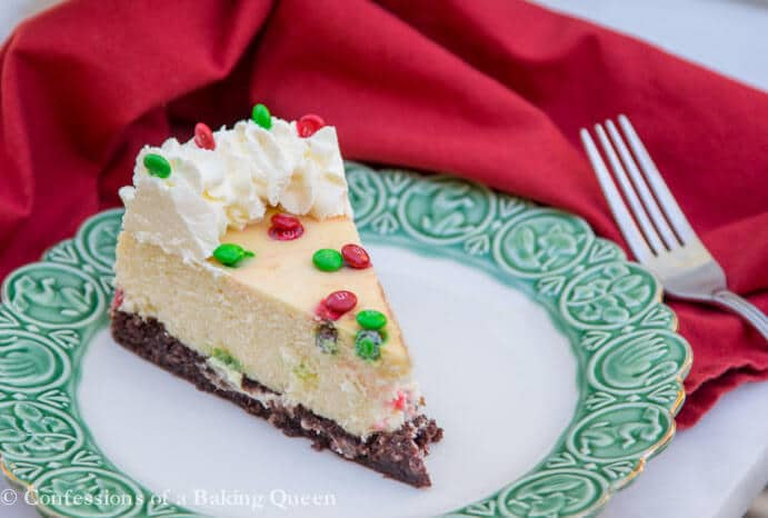 Brownie Bottom Cheesecake on a white and green plate with a red linen and fork next to it on a white surface