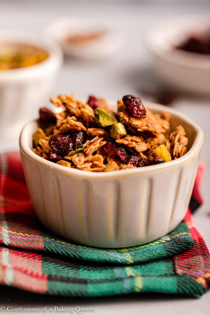 chrismas granola in a small bowl on a red and green checkered linen with bowls of ingredients in the background on a grey background