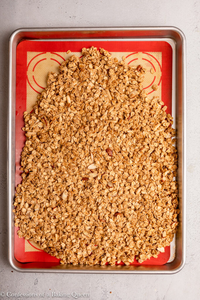 granola patted into a silpat lined baking sheet before baking sitting on a grey surface