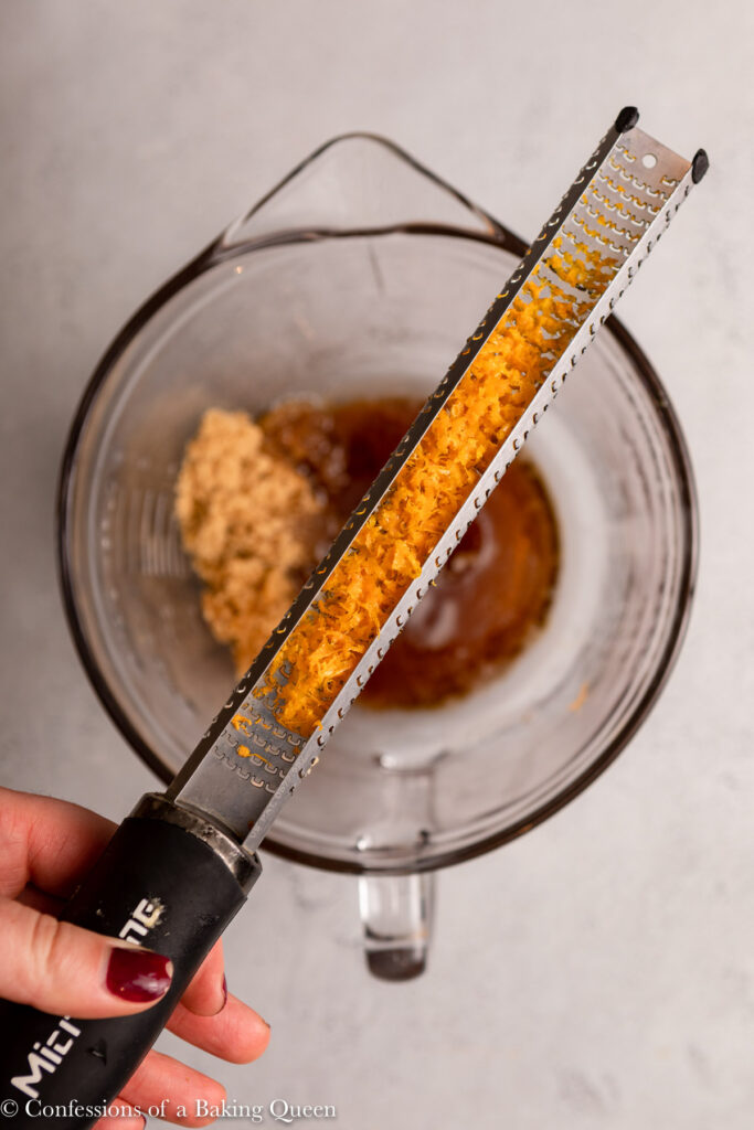 orange zested in a microplane zester over a bowl of ingredients on a grey surface