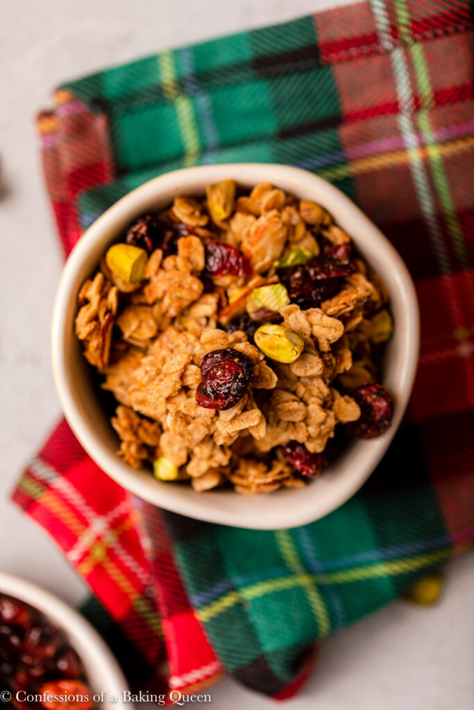 overhead view of cranberry pistachio granola in a small bowl on a red and green checkered linen on a grey surface