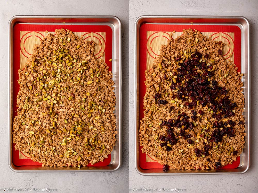 pistachios added to granola then cranberries added on a sheet pan on a light grey surface