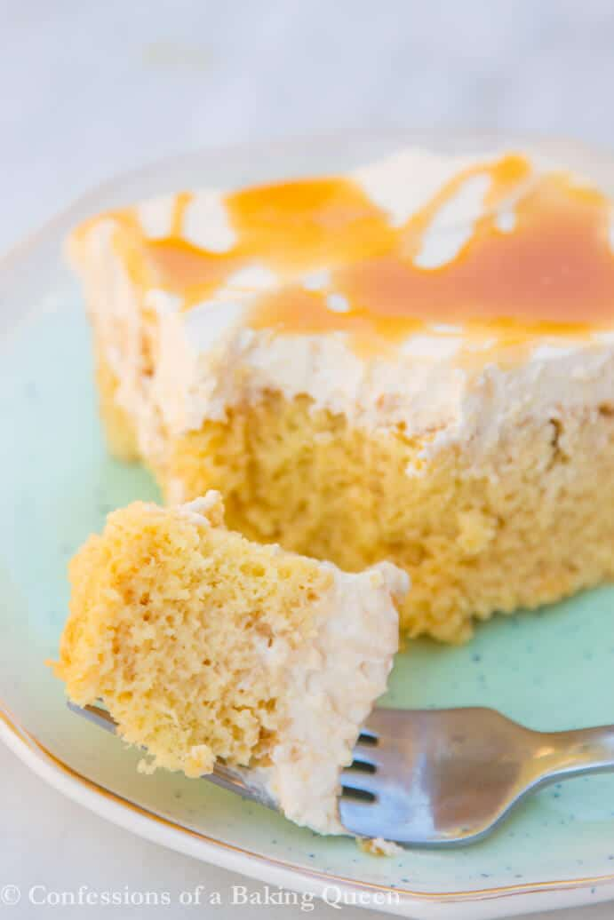 Salted Caramel Tres Leches Cake served on a blue plate with a fork taking a bite