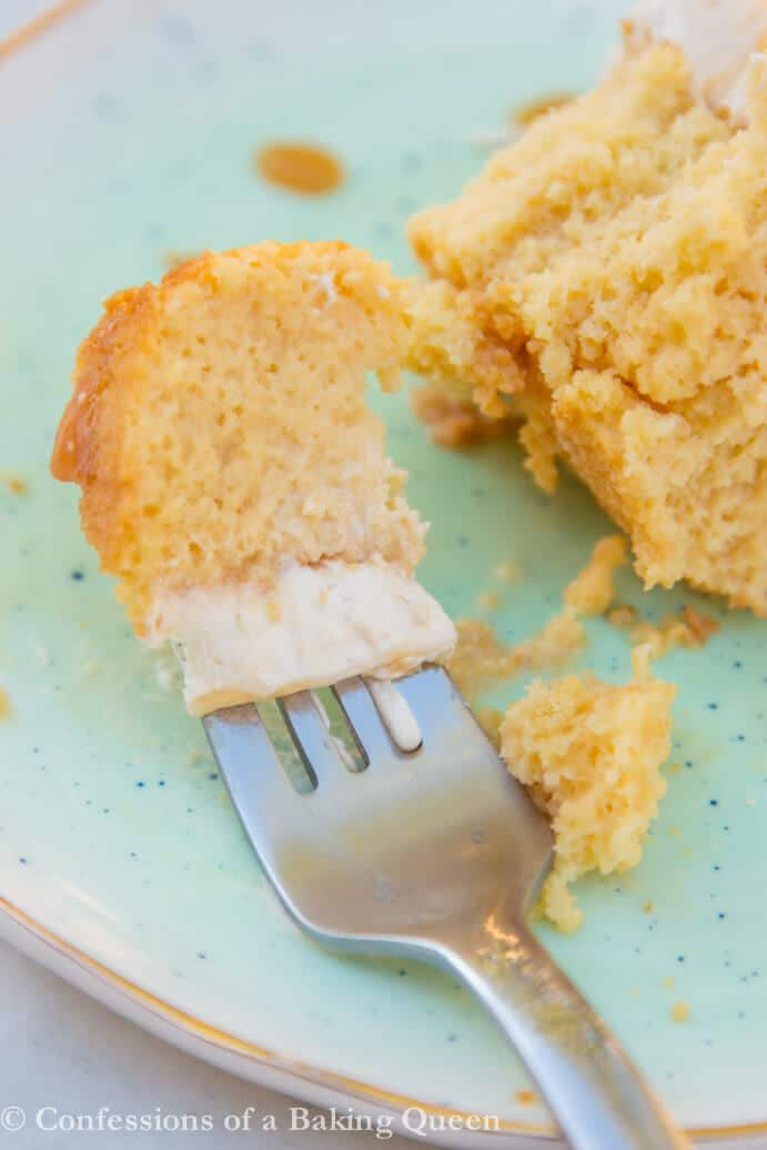 bite of salted caramel tres leches cake on a silver fork on a light green plate