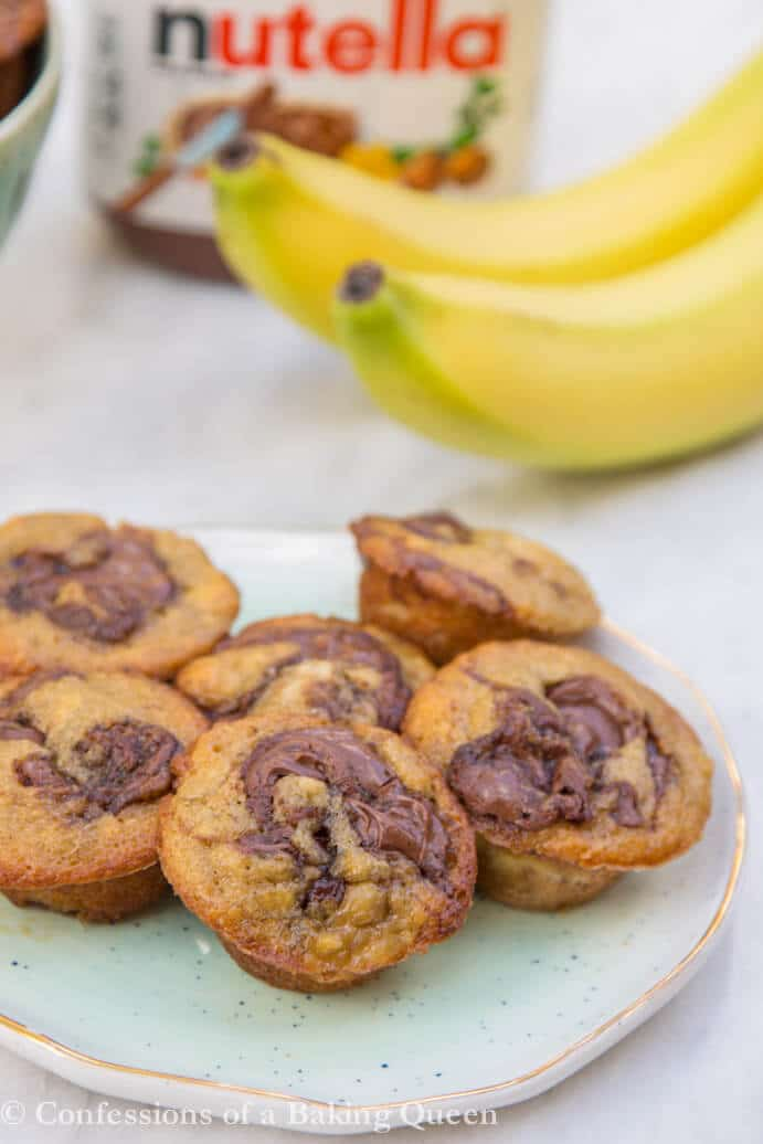 nutella banana muffins on a blue plate with bananas and nutella in background