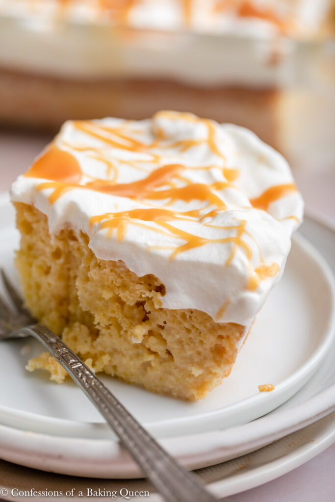 salted caramel tres leches cake on a white plate with a fork on a light pink surface