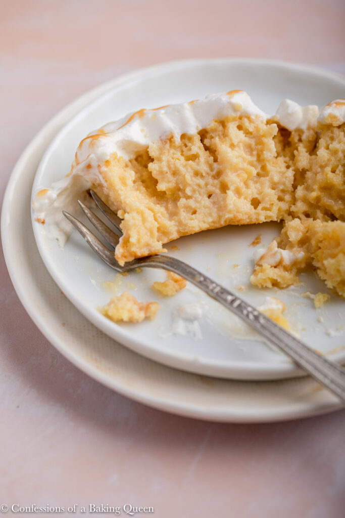 slice of half eaten salted caramel tres leches cake on a white plate with a fork on a light pink surface