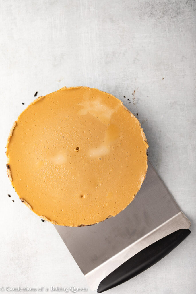 coffee cheesecake being released from pan with a large cake mover