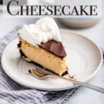 slice of baked coffee cheesecake on a white plate with a fork sitting on a blue linen on a grey surface with a cup of coffee and cheesecake in the background