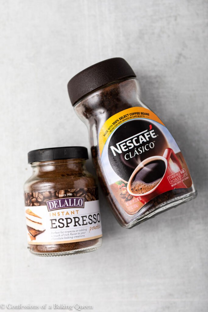 instant coffee container and jar of espresso powder on a grey surface
