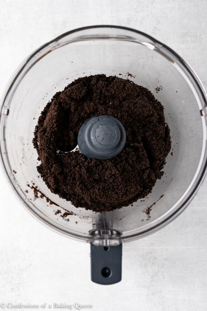 oreo crust crumbs in a food processor bowl on a grey surface