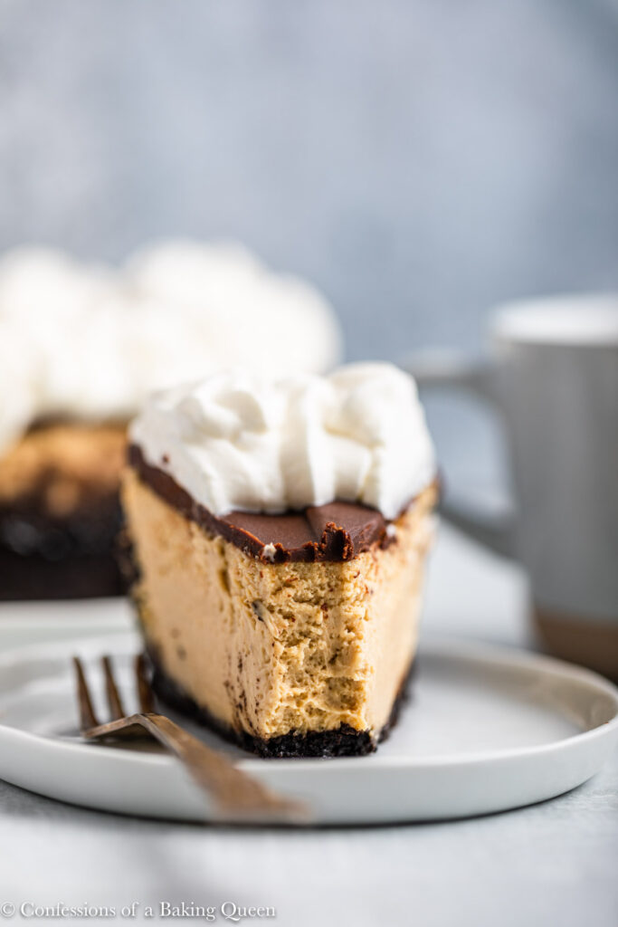 slice of espresso cheesecake on a white plate with a fork and cheesecake and coffee in the background (