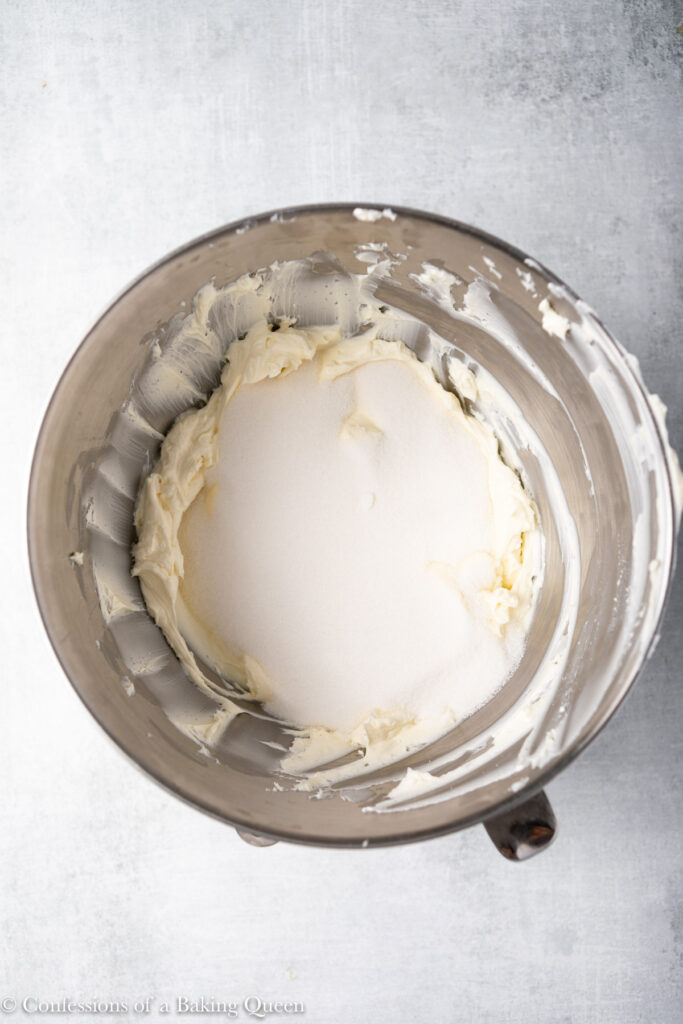 sugar mixed into cream cheese in a metal bowl on a grey surface