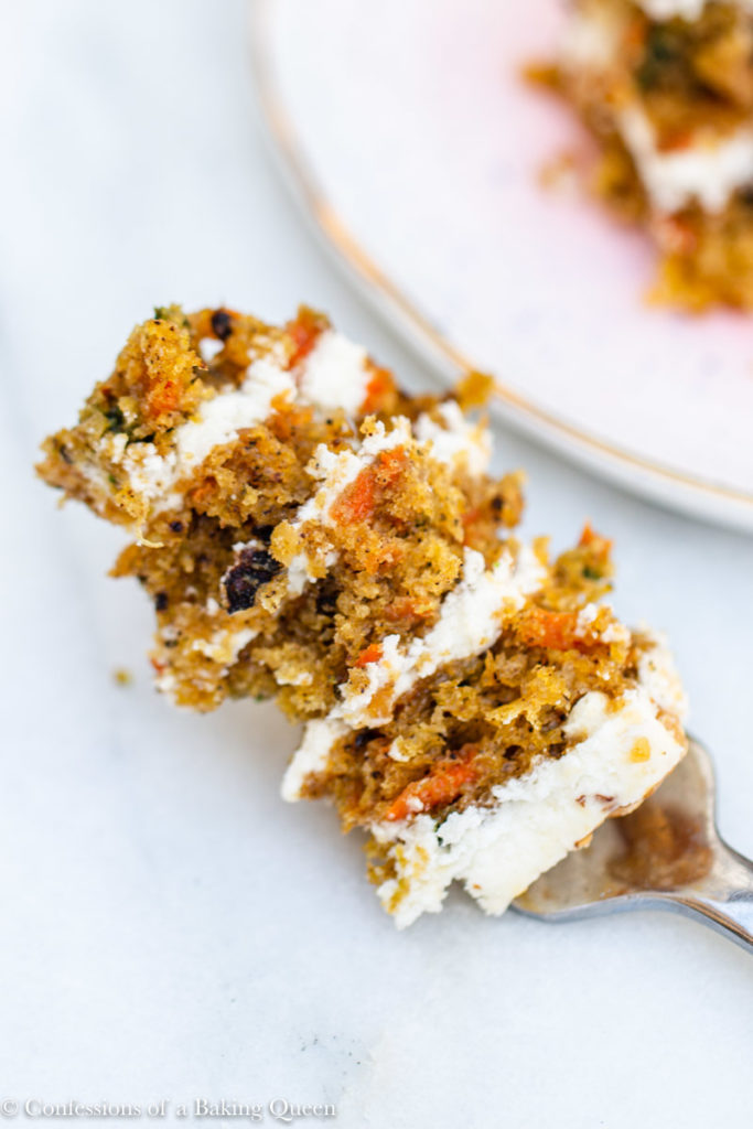 bite of carrot cake on a silver fork on a white background