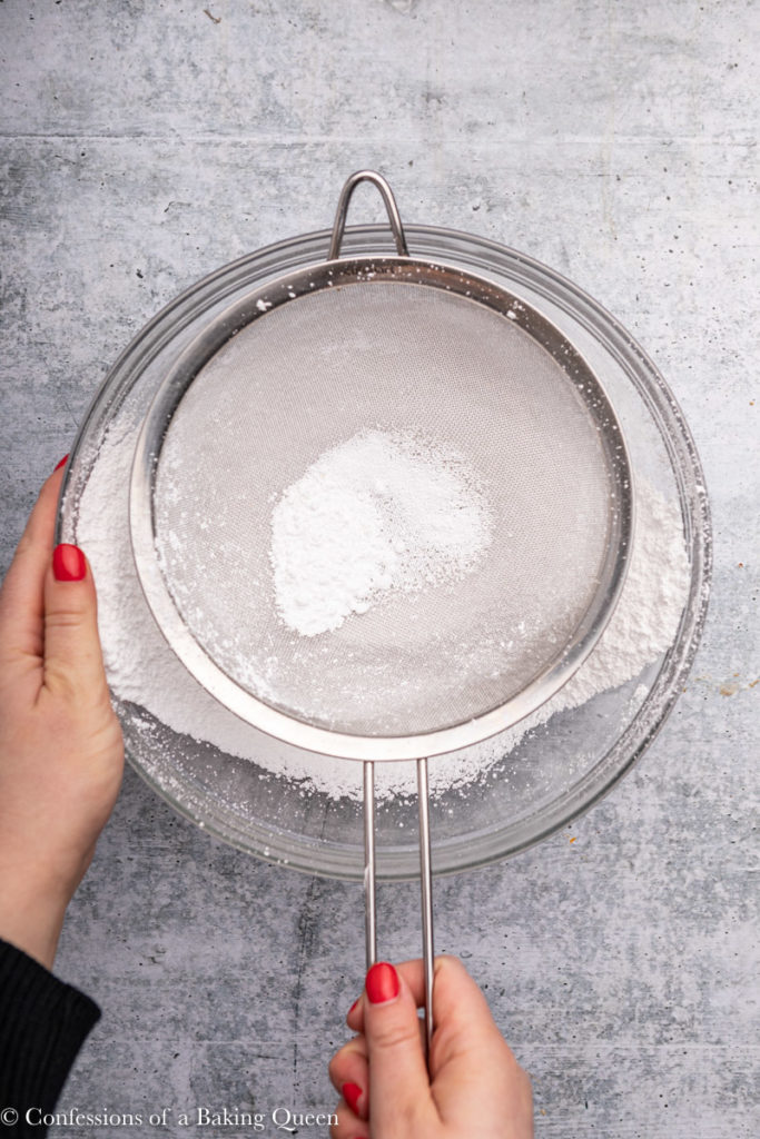 hand holding sieve with powdered sugar on a grey background