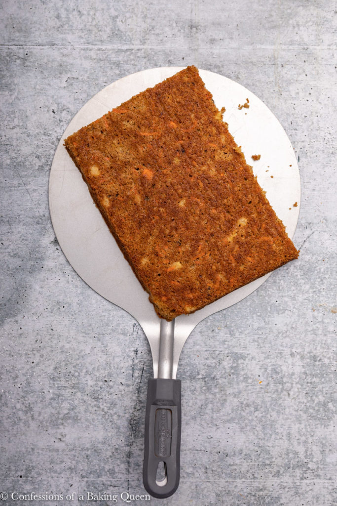 large spatula holding a layer of carrot cake on a grey background