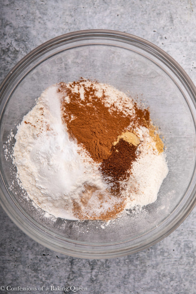 spices, salt, and baking powder added to flour in a glass bowl on a grey background