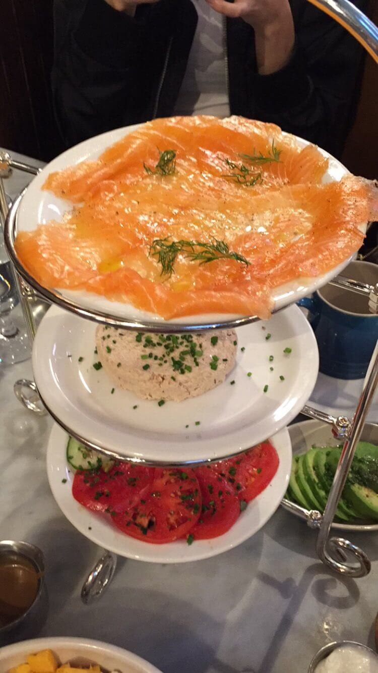 three tier plate of smoked salmon, fish salad, and tomatoes on a table at Sadelles in New York