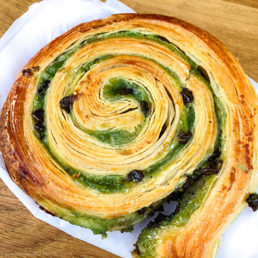pastry snail showing the green filling with chocolate chips on a wood board