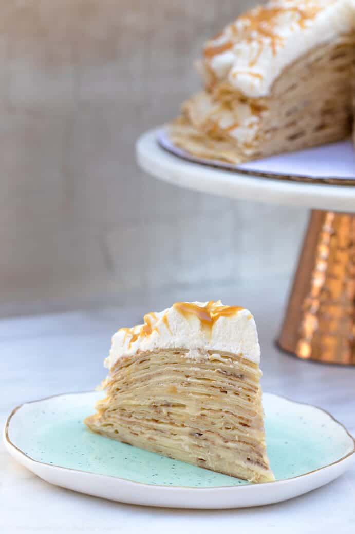 salted caramel crepe cake on a blue plate with the full crepe cake in background