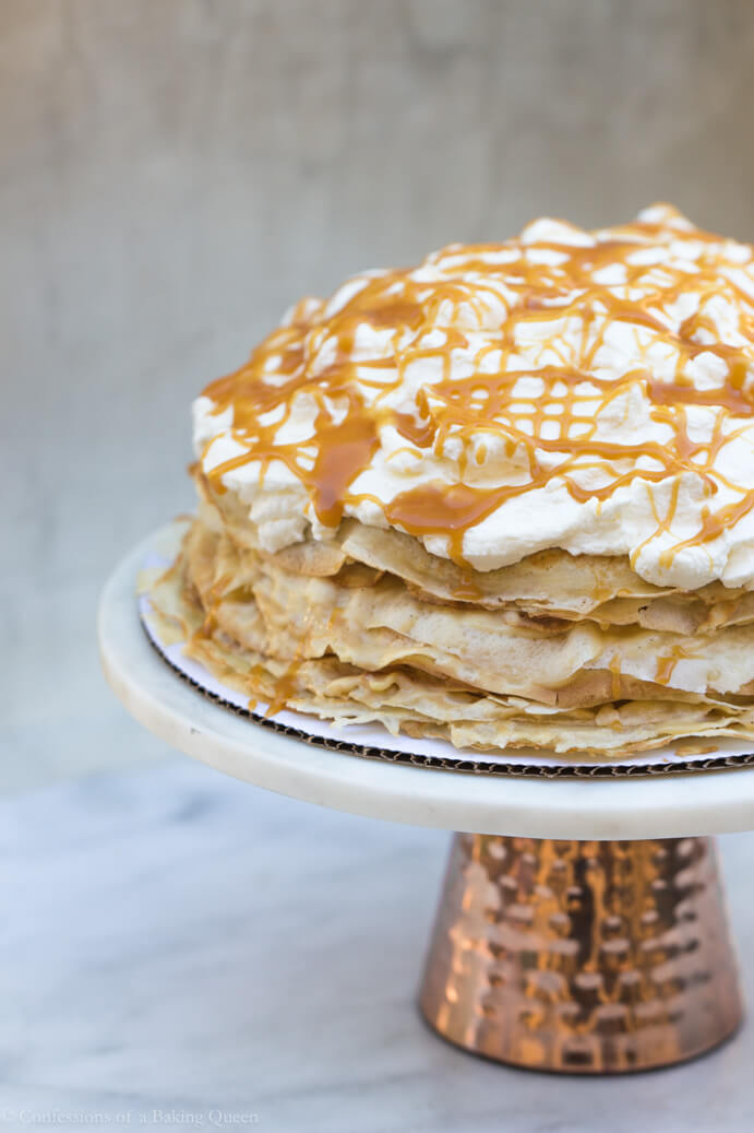 Salted Caramel Crepe Cake on a cake stand with copper bottom and on a white marble background
