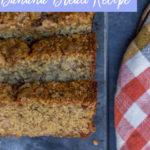 oat flour banana bread recipe sliced on a dark surface with an orange tea towel next to the bread