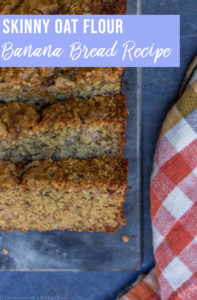 oat flour banana bread recipe sliced on a dark surface with an orange tea towel next to the bread