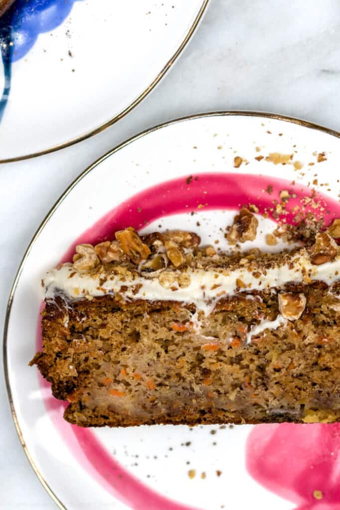 carrot pineapple banana loaf cake on a white and pink plate on a marble background on a grey background