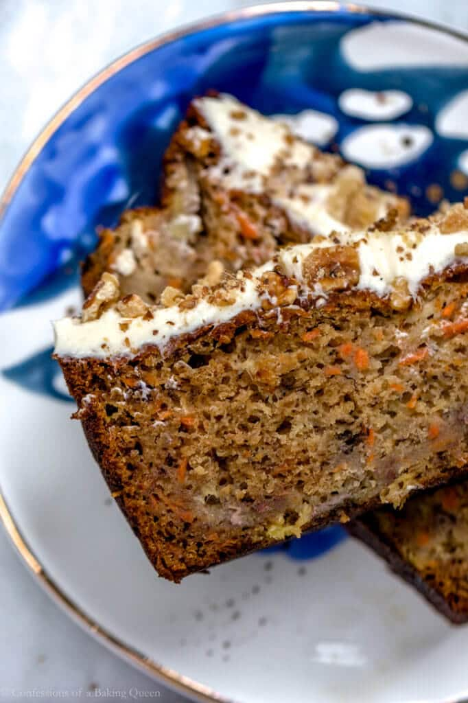 carrot pineapple banana loaf cake slice stacked on top of each other on blue and white plate on a grey background