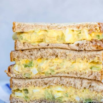 stack of egg salad sandwiches on a light blue stripped plate on a grey background