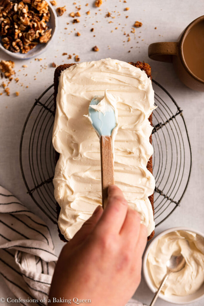 hand holding a spatula spreading cream ceese frosting on top of the cake on a light grey surface with a bowl of nuts and cup of coffee