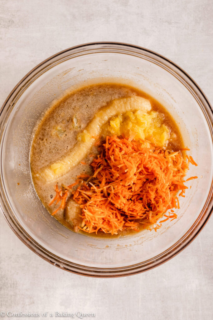 shredded carrots, pineapple, and banana added to wet ingredients in a glass bowl on a light grey surface