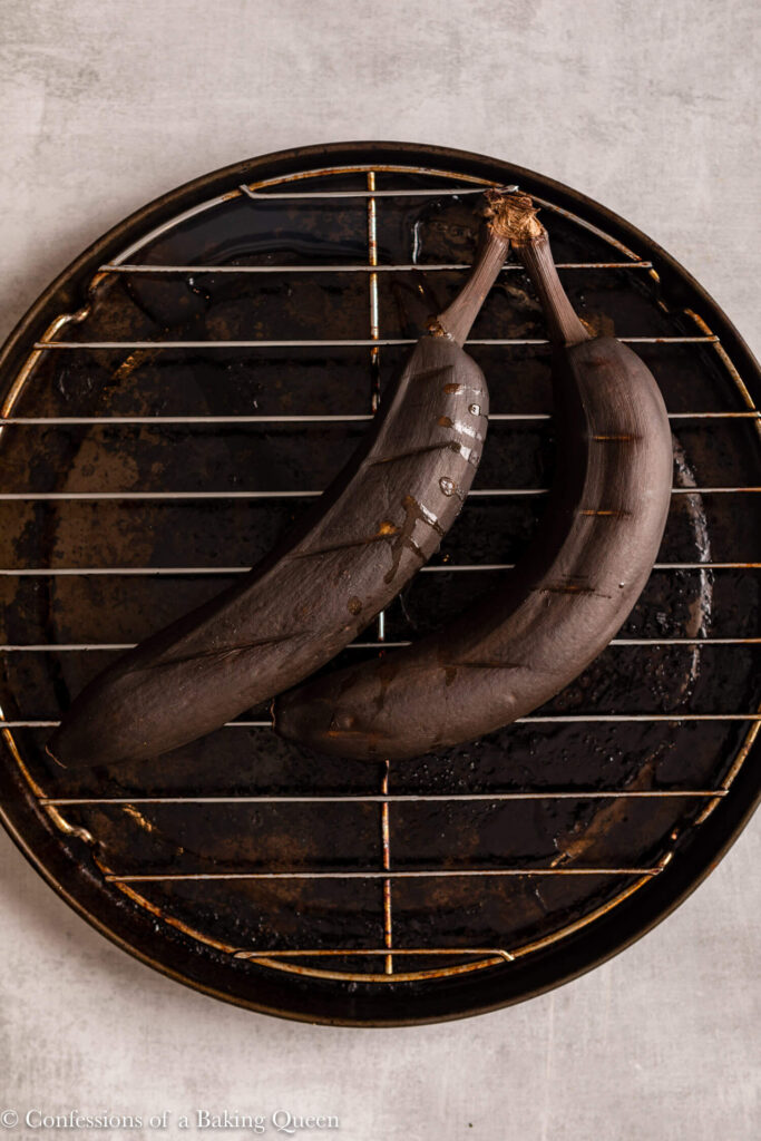 two bananas baked in the oven wtih their skin on a metal baking pan on a light grey surface