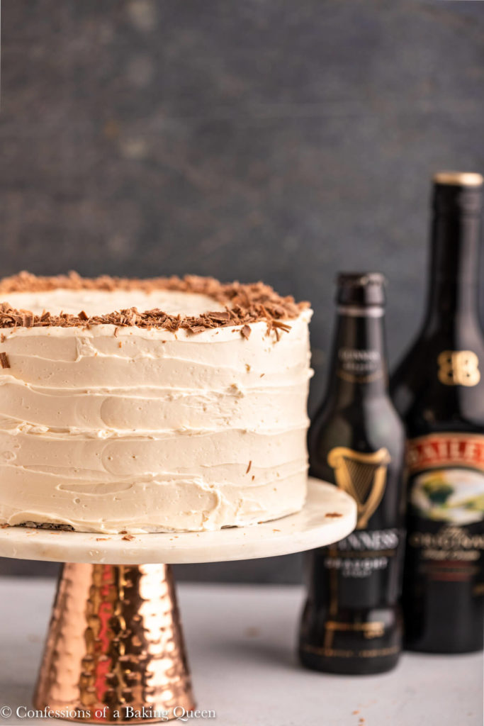 cake on a cake stand next to a bottle of Guinness and a bottle of Baileys