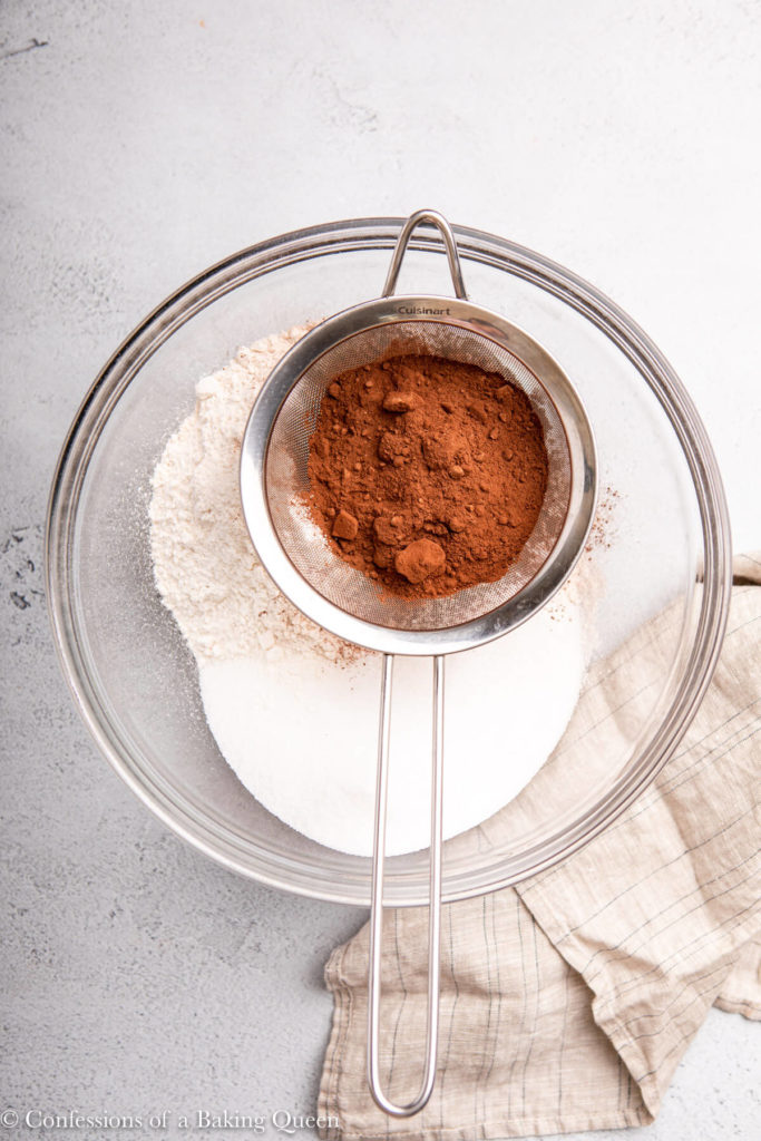 cocoa powder in metal sieve added to dry ingredients