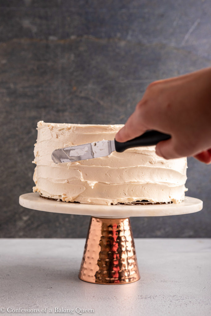 hand using a angled spatula to decorate frosting on a cake