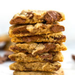 ultimate chocolate chunk cookies broken open and stacked on top of each other on white marble
