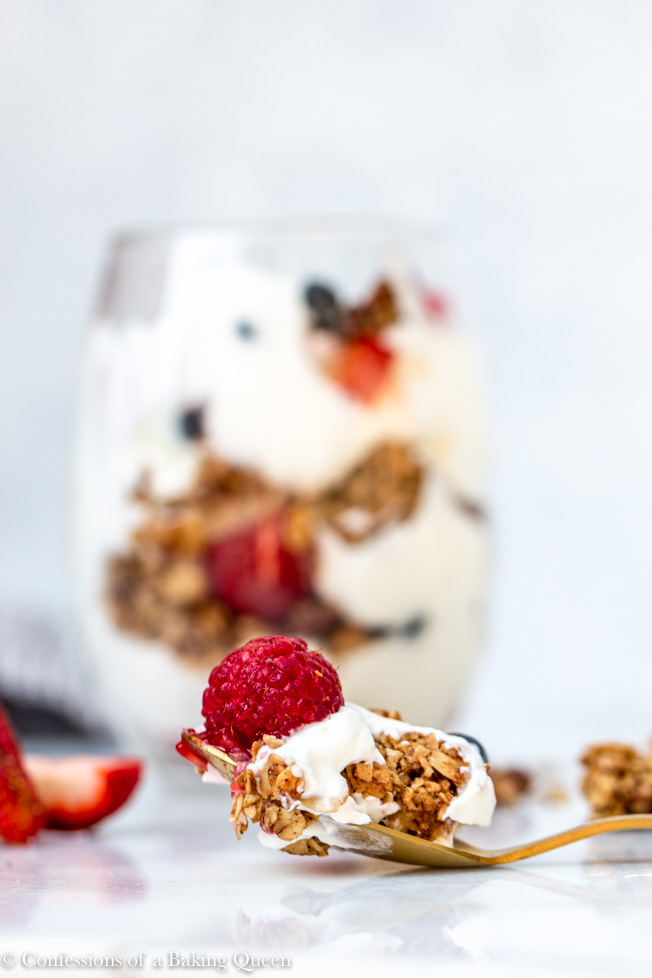 spoonful of banana nut granola with berries and yogurt on a gold spoon with the yogurt parfait in the background